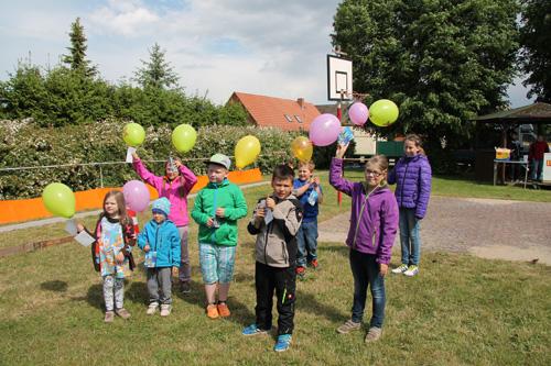 Kinder lassen Luftballons mit Kartengrüßen steigen